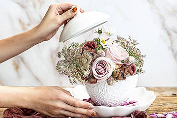 秋色のお花を束ねたシックなアレンジメントを白い器に生けた写真