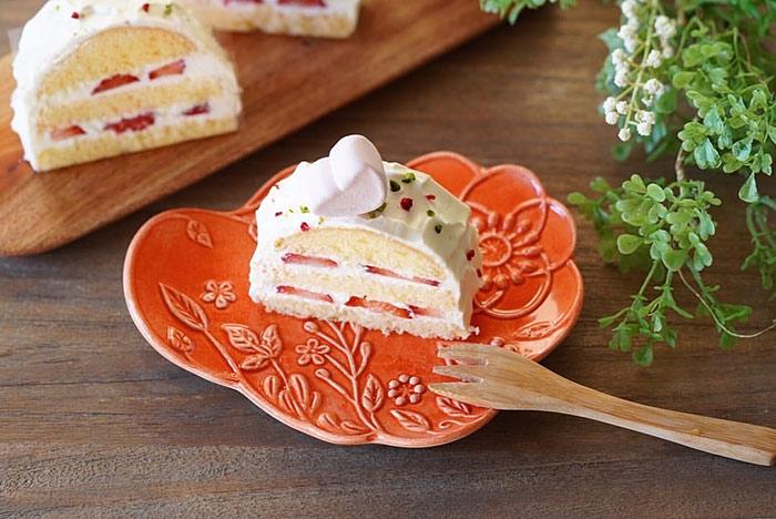 苺のケーキがのったオレンジ色の小皿
